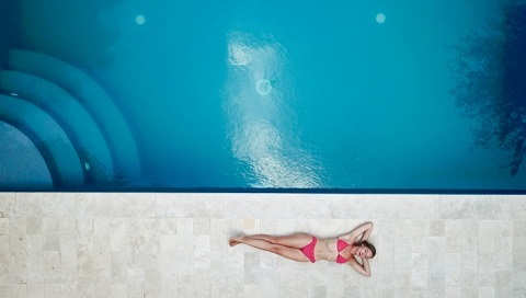 Private oasis woman lying on floor near pool 1460742 60th Anniversary 480